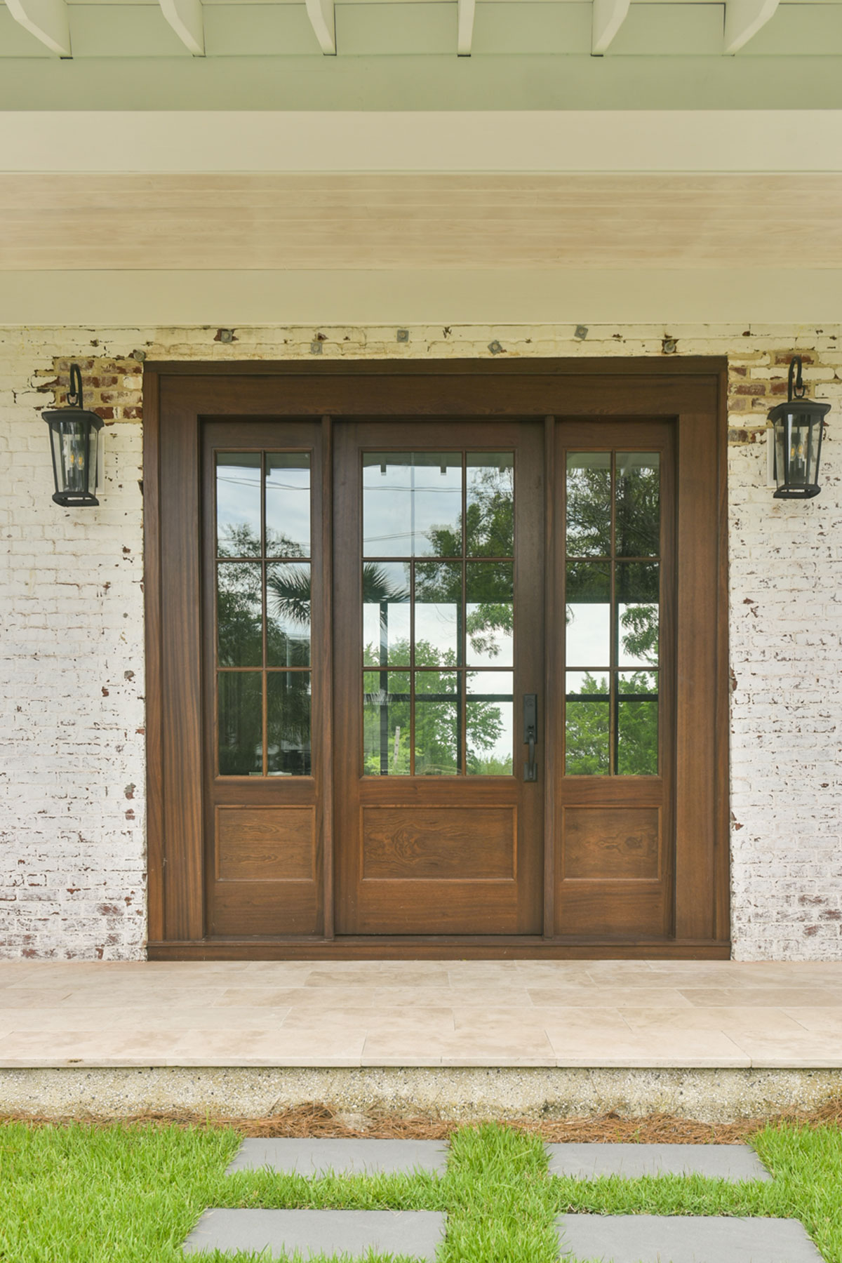 Wood stained front door with extra wide sidelights brings in natural light to the interior of the home
