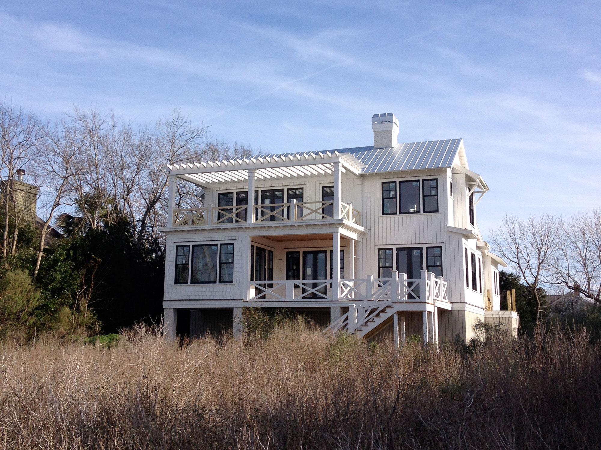 Backside view of coastal home with porches and metal room