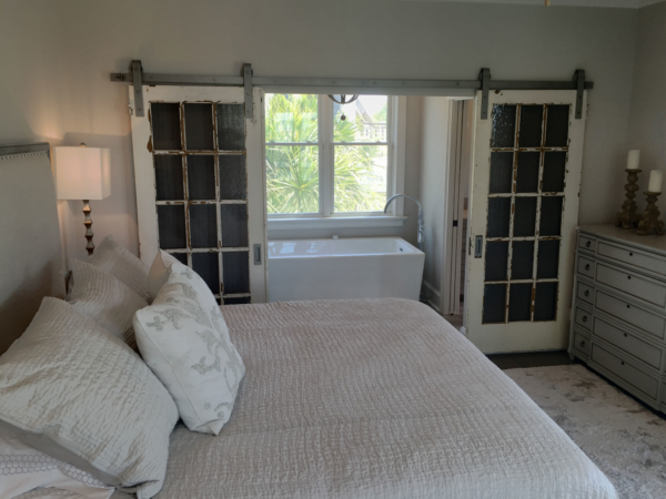 Salvaged doors open to master bath addition on balcony