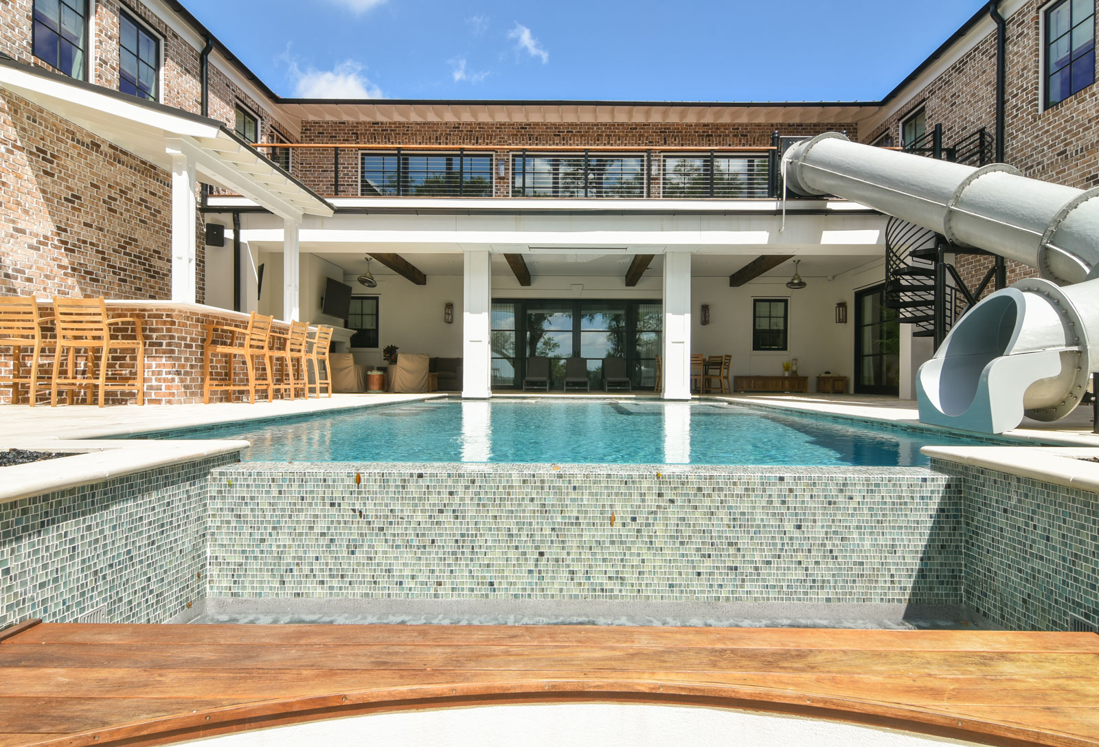 Infinity edge pool and two story water slide in backyard entertaining