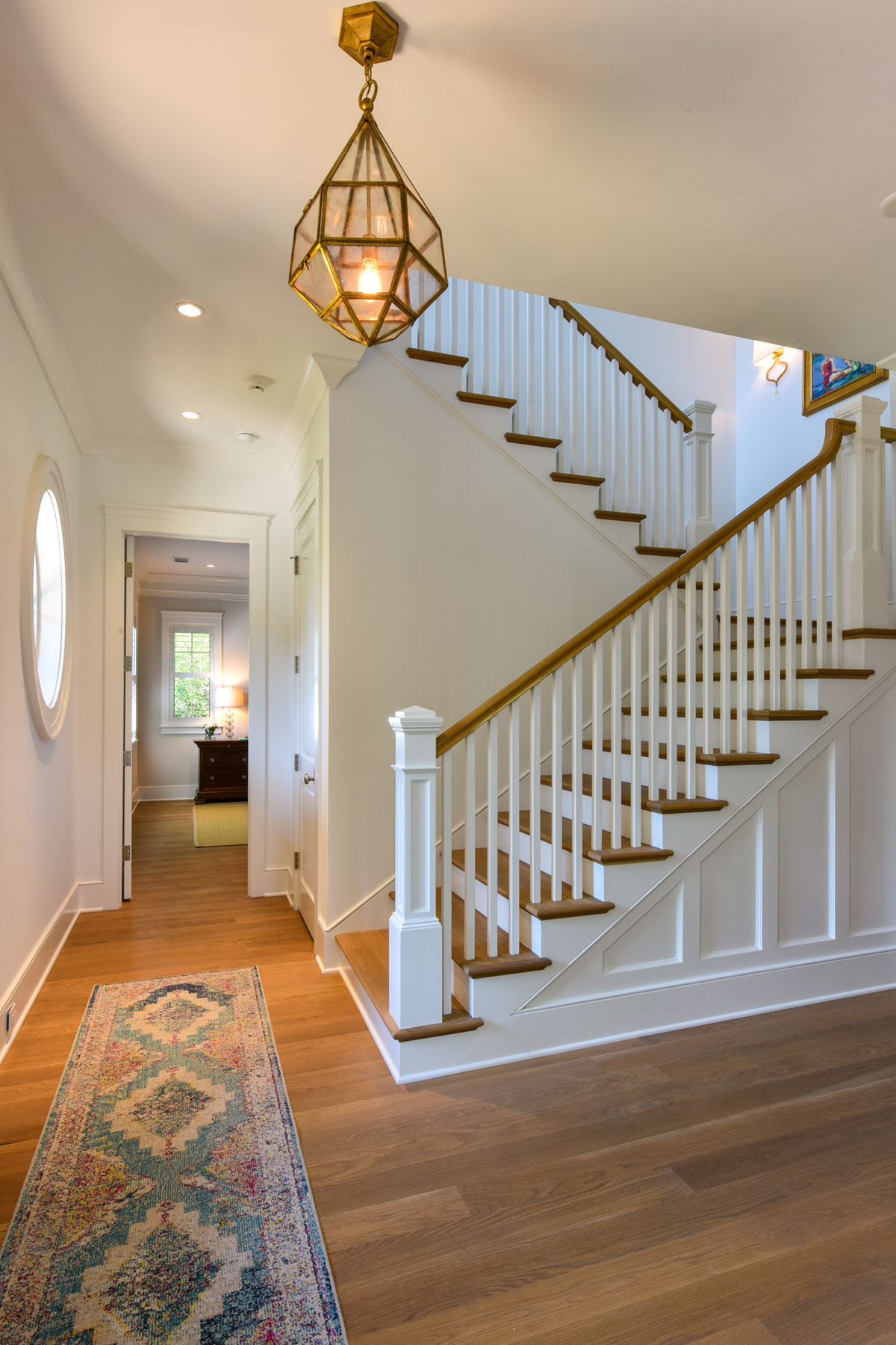 Front staircase with white painted trim and light wood floor