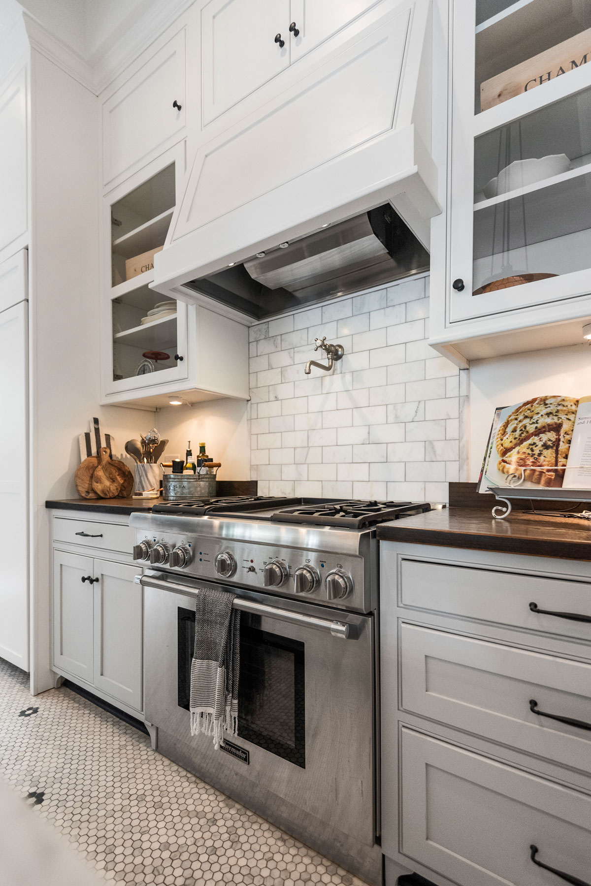Kitchen renovation with white cabinets and white vent hood over large range