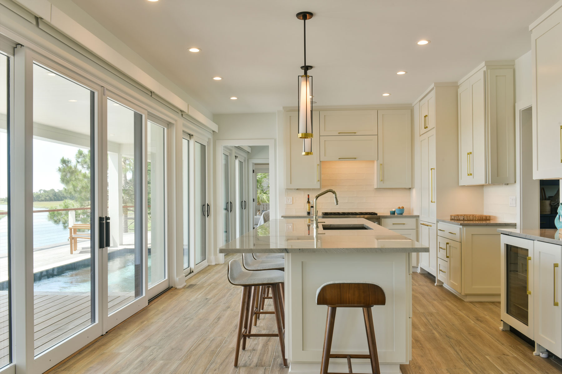 Kitchen opening to pool deck in home designed by Swallowtail Architecture